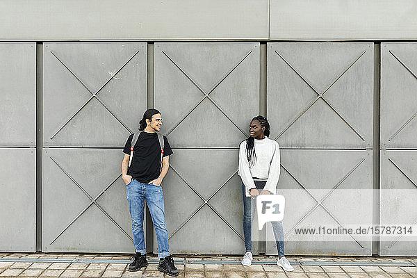 Young man smiling at woman at a grey wall
