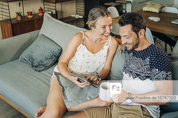 Glückliches  entspanntes Paar sitzt auf einer Couch im Wohnzimmer und teilt sich eine Tafel
