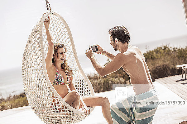 Man taking a picture of a young woman in hanging chair at the poolside