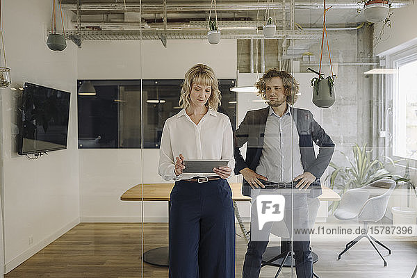 Businessman and businesswoman using tablet in office