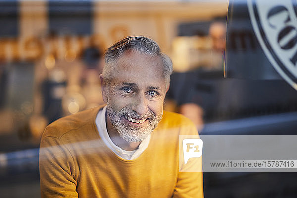 Portrait of smiling mature man behind glass pane in a cafe