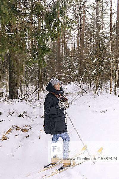 Lächelnde Frau auf Skiern im Winterwald