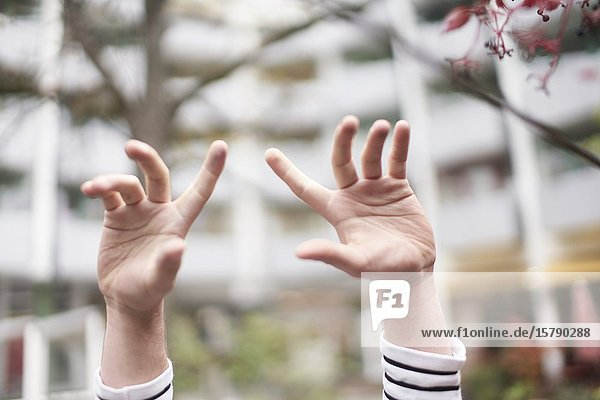 Close-up image of young man's hands raised.