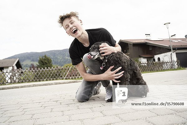 Teenager playing with his dog  in Gaissach  Bavaria  Germany.