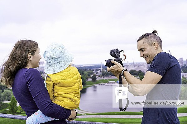 Family in park  taking photos. Munich  Germany.