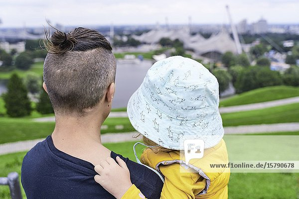 Father and daughter in park  looking at view. Munich  Germany.