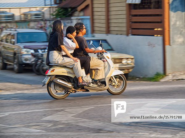 Three people on a motor scooter  Chiang Mai  Thailand.