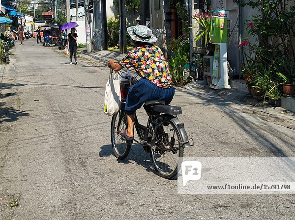 Woman on bicycle in a lane  Chiang Mai  Thailand.