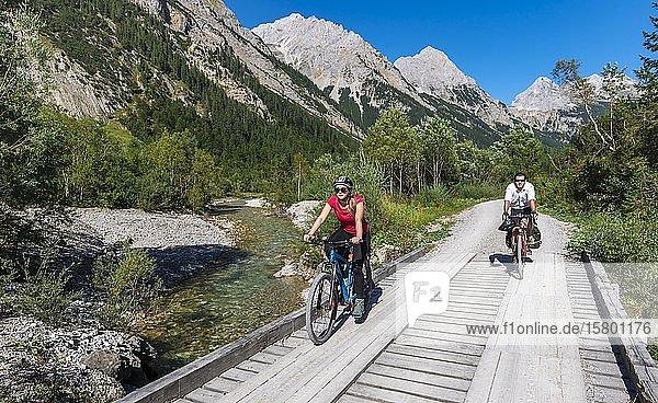 Fahrradfahrer  Mountainbiker radeln auf Brücke über Gebirgsbach  Schotterweg zum Karwendelhaus  Karwendeltal  Tirol  Österreich  Europa