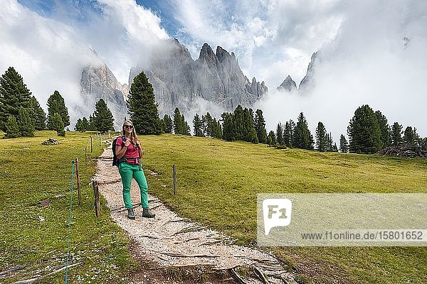 Young woman  hiker on a hiking trail  in the back Sass Rigais  Parco Naturale Puez Odle  South Tyrol  Italy  Europe