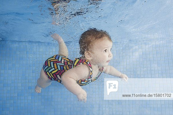 Baby im Badeanzug schwimmt unter Wasser im Schwimmbad  Ukraine  Europa