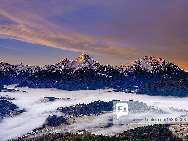 Sonnenaufgang an den Gipfeln vom Steinernen Meer  Watzmann und Hochkalter  Nebel im Talkessel von Berchtesgaden  Winterlandschaft  Berchtesgaden  Schönau am Königssee  Berchtesgadener Land  Oberbayern  Bayern  Deutschland  Europa