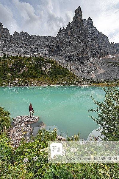 Junge Frau  Wanderin am türkisgrünen Sorapis See  Lago di Sorapis  Bergspitze Dito di Dio  Dolomiten  Belluno  Italien  Europa