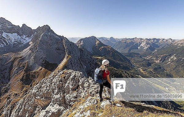Junge Frau  Bergsteigerin mit Kletterhelm blickt auf Berglandschaft  Wanderung zur Ehrwalder Sonnenspitze  hinten Grünstein und Westliche Marienbergspitze  Ehrwald  Mieminger Kette  Tirol  Österreich  Europa