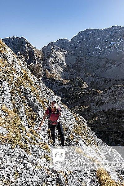 Bergsteigerin  junge Frau mit Kletterhelm wandert an steilem felsigen Hang  Wanderweg zur Ehrwalder Sonnenspitze  Ehrwald  Mieminger Kette  Tirol  Österreich  Europa