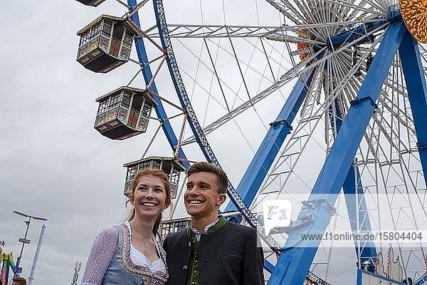 Junges Paar in Tracht vor dem Riesenrad  Wiesn  Wies´n  Oktoberfest  München  Oberbayern  Bayern  Deutschland  Europa
