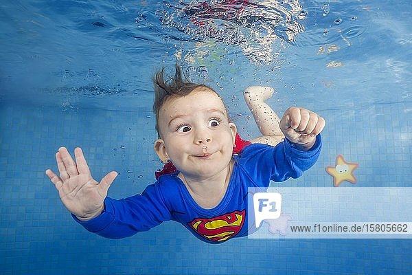 Kleiner Junge im Superman Kostüm taucht im Schwimmbad unter Wasser  Frontansicht  Ukraine  Europa