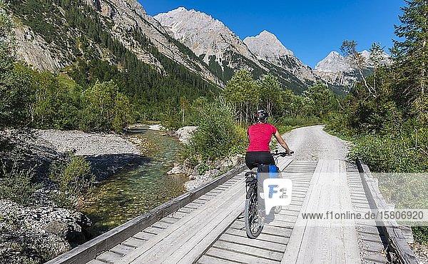 Fahrradfahrer  Mountainbikerin radelt auf Brücke über Gebirgsbach  Schotterweg zum Karwendelhaus  Karwendeltal  Tirol  Österreich  Europa