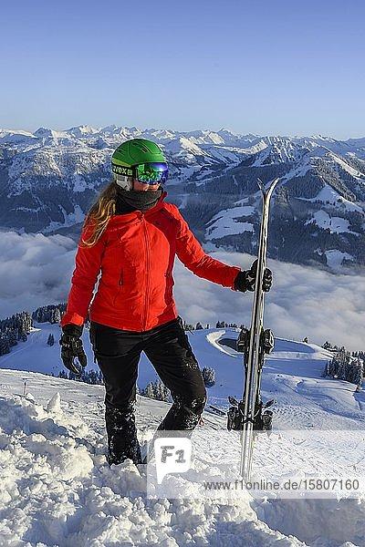 Skifahrerin mit Skihelm und Ski steht an der Skipiste  hinten Bergpanorama  SkiWelt Wilder Kaiser  Brixen im Thale  Tirol  Österreich  Europa