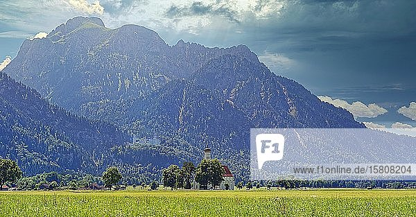 Mächtiges Säuling Bergmassiv der Ammergauer Alpen mit den Märchenschloss Neuschwanstein und der kleinen Kirche St. Coloman inmitten einer saftig grünen Wiese  Hohenschwangau  Füssen  Bayern  Deutschland  Europa