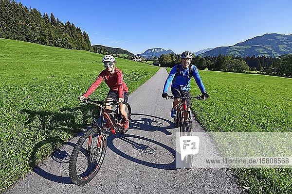 Zwei Radfahrer mit Elektromountainbikes auf dem Penningberg  Kitzbüheler Alpen  Tirol  Österreich  Europa Zwei Radfahrer mit Elektromountainbikes auf dem Penningberg, Kitzbüheler Alpen, Tirol, Österreich, Europa