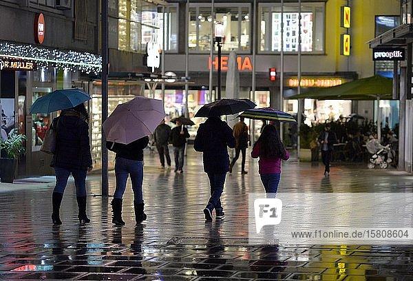 Menschen mit Regenschirm in der nächtlichen City  Stuttgart  Baden-Württemberg  Deutschland  Europa