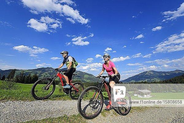 Zwei Radfahrer mit Elektromountainbikes auf dem Glantersberg mit Blick auf die Hohe Salve  Kitzbüheler Alpen  Tirol  Österreich  Europa
