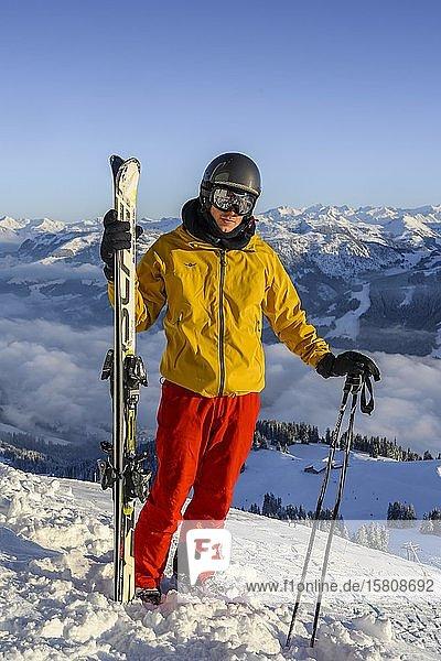 Skifahrer steht an der Skipiste und hält Ski  Blick in die Kamera  Gipfel Hohe Salve  SkiWelt Wilder Kaiser Brixenthal  Hochbrixen  Tirol  Österreich  Europa