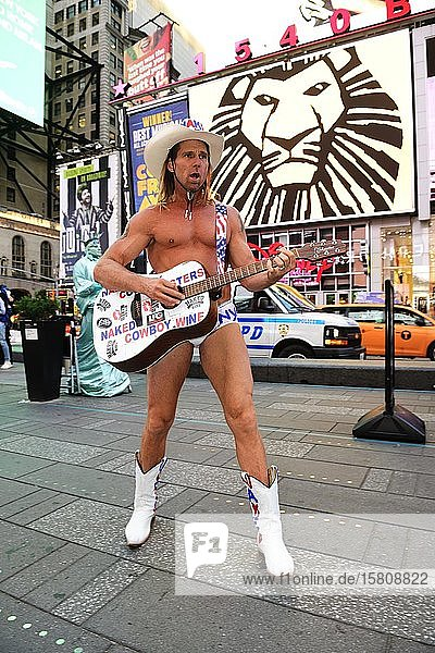 Robert Burck  the naked cowboy  is having his picture taken with tourists in Times Square  Manhattan  New York City  New York State  USA  North America