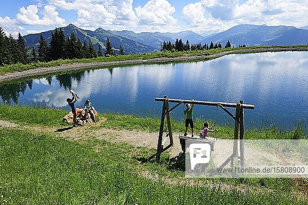 Family playing during a hike at the storage lake at the middle station  Hohe Salve  Hopfgarten  Brixental  Kitzbüheler Alps  Tyrol  Austria  Europe