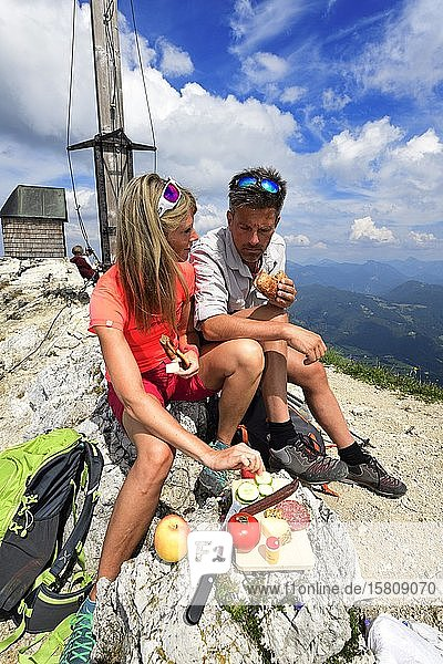 Hikers having a snack on the summit of the Geigelstein  Sachrang  Chiemgau  Upper Bavaria  Bavaria  Germany  Europe