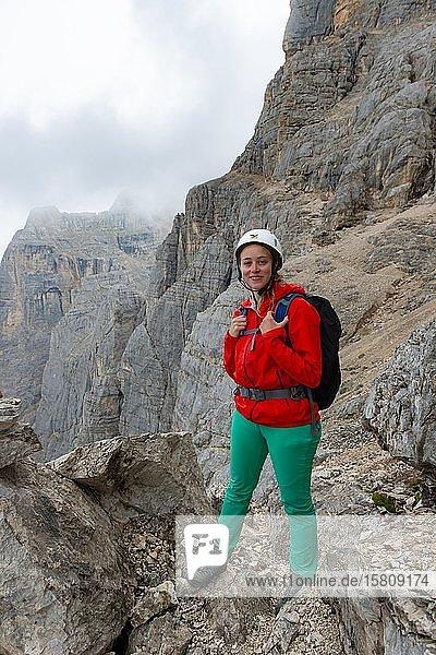 Junge Frau  Wanderin mit Kletterhelm vor einer Felswand  Klettersteig Via ferrata Francesco Berti  Sorapiss Umrundung  Dolomiten  Belluno  Italien  Europa