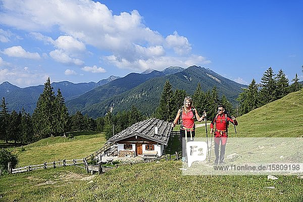 Hikers in front of the Oberauerbrunstalm  Schleching  Chiemgau  Upper Bavaria  Bavaria  Germany  Europe