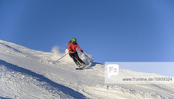 Skifahrerin fährt steile Abfahrt hinunter  schwarze Piste  blauer Himmel  SkiWelt Wilder Kaiser  Brixen im Thale  Tirol  Österreich  Europa