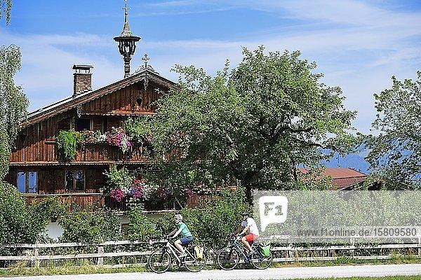 Radfahrer vor Bauernhaus mit Blumenschmuck am Penningberg  Hopfgarten  Kitzbüheler Alpen  Tirol  Österreich  Europa