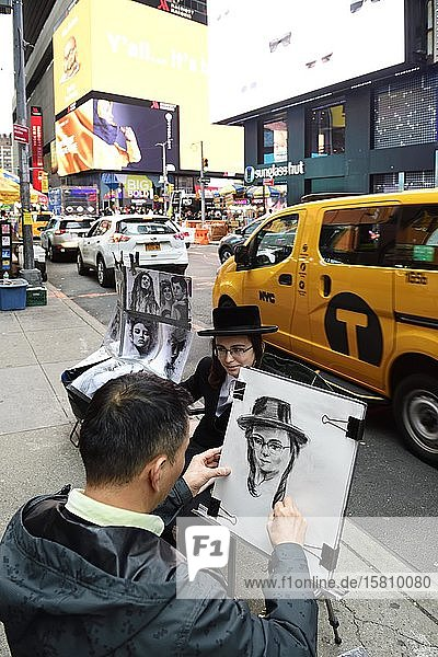 Ein jüdisch-orthodoxer Junge mit Schläfenlocken und Hut wird am Times Square von einem Straßenmaler porträtiert  Manhattan  New York City  New York State  USA  Nordamerika