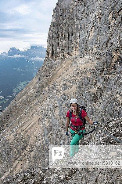 Junge Frau  Wanderin gesichert an einem Stahlseil beim Klettern an einer Felswand  Klettersteig Via ferrata Francesco Berti  Sorapiss Umrundung  Dolomiten  Belluno  Italien  Europa