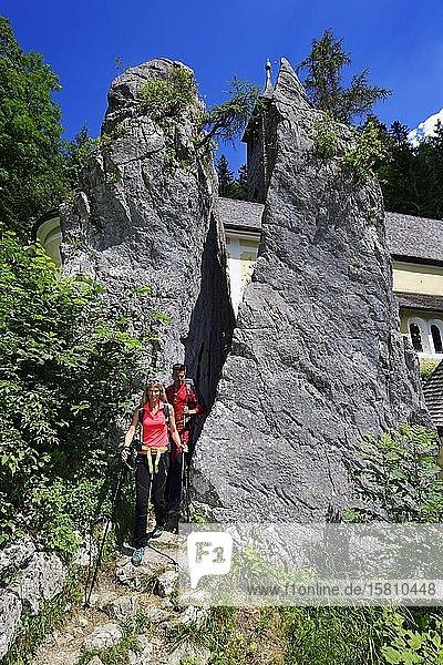 Hikers walk through the split rock at Klobenstein  Tyrol  Austria  Europe