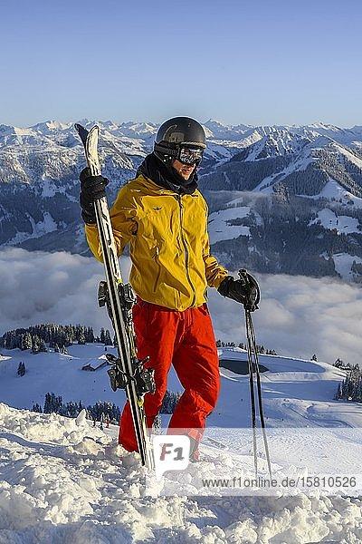 Skifahrer steht an der Skipiste und hält Ski  vor Bergpanorama  Gipfel Hohe Salve  SkiWelt Wilder Kaiser Brixenthal  Hochbrixen  Tirol  Österreich  Europa