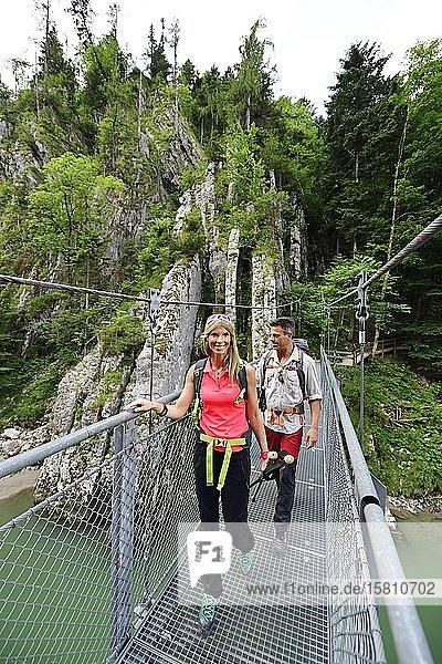 Hikers on the suspension bridge of the Grossache  Tiroler Ache  Klobenstein  Tyrol  Österreic