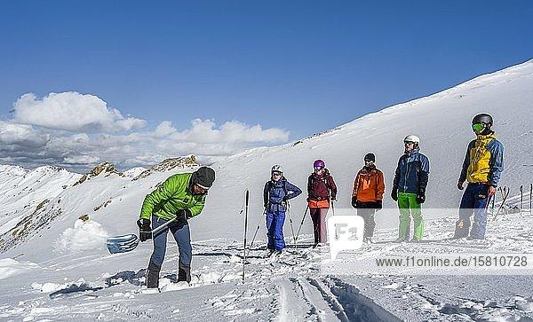 Skitourengeher im Schnee  Gruppenleiter und Gruppe bei einer Lawinenübung  prüfen des Schneeprofils  Wattentaler Lizum  Tuxer Alpen  Tirol  Österreich  Europa