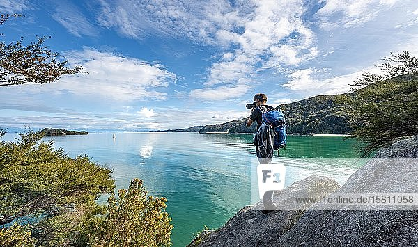 Photographer stands on a rock and takes pictures  Stillwell Bay  Abel Tasman Coastal Track  Abel Tasman National Park  Tasman  South Island  New Zealand  Oceania