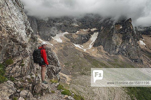 Junge Frau  Wanderin beim Klettern in einem Klettersteig  Via ferrata Vandelli  Sorapiss Umrundung  Berge mit tiefhängenden Wolken  Dolomiten  Belluno  Italien  Europa
