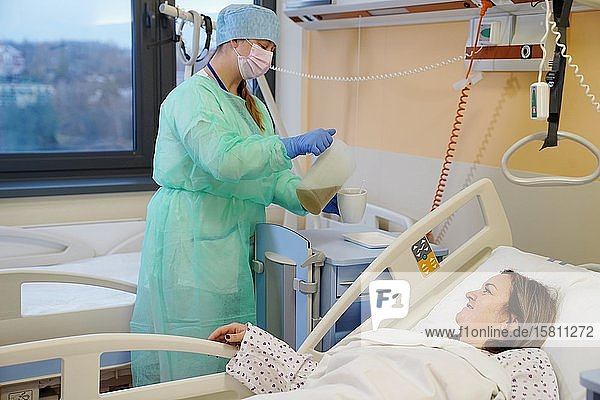 Krankenschwester an der Infektionsstation im Krankenhaus gießt Tee zum Patienten  Karlovy Vary  Tschechien  Europa
