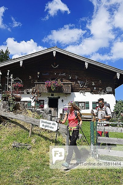 Hikers in front of the Chiemhauser Alm  Schleching  Chiemgau  Upper Bavaria  Bavaria  Germany  Europe