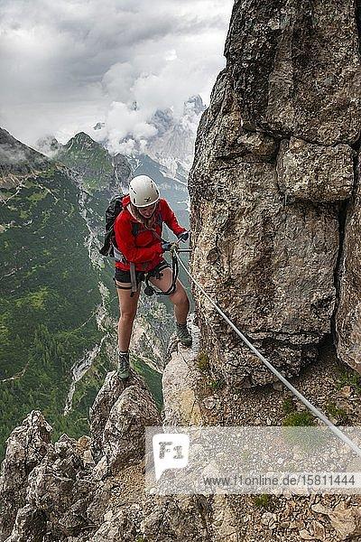 Junge Frau  Wanderin beim Klettern an einer Felskante in einem Klettersteig  Via ferrata Vandelli  Sorapiss Umrundung  Berge mit tiefhängenden Wolken  Dolomiten  Belluno  Italien  Europa
