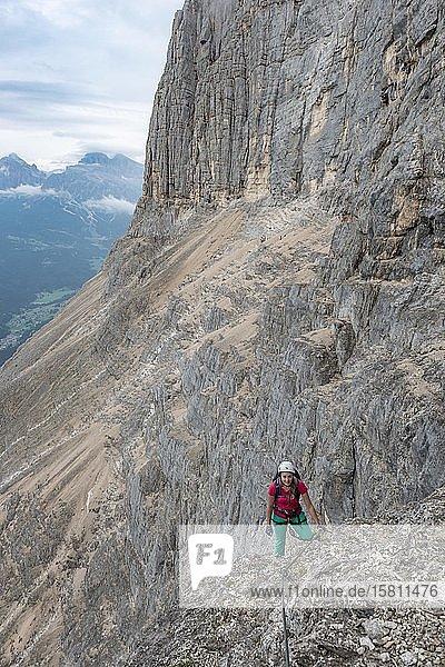 Junge Frau  Wanderin gesichert mit Kletterhelm an einer Felswand  Klettersteig Via ferrata Francesco Berti  Sorapiss Umrundung  Dolomiten  Belluno  Italien  Europa