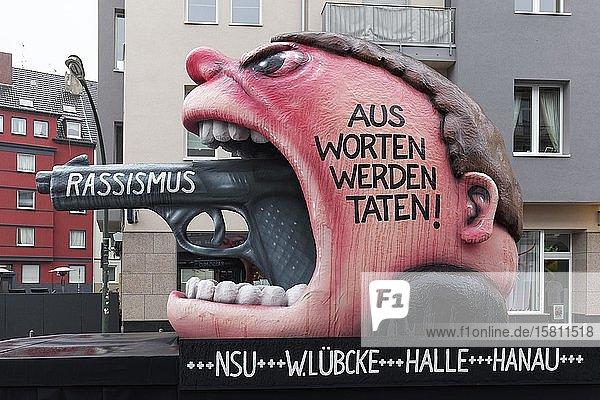 Mottowagen von Jacques Tilly  Kopf mit aufgerissenem Mund  aus dem eine Pistole mit Aufschrift Rassismus ragt  Aus Worten werden Taten  Rosenmontagszug 2020  Düsseldorf  Nordrhein-Westfalen  Deutschland  Europa