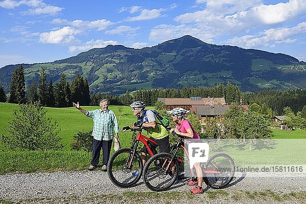 Old farmer's wife shows two cyclists with electric mountain bikes the way to the Glantersberg  in the background the Hohe Salve  Kitzbühel Alps  Tyrol  Austria  Europe