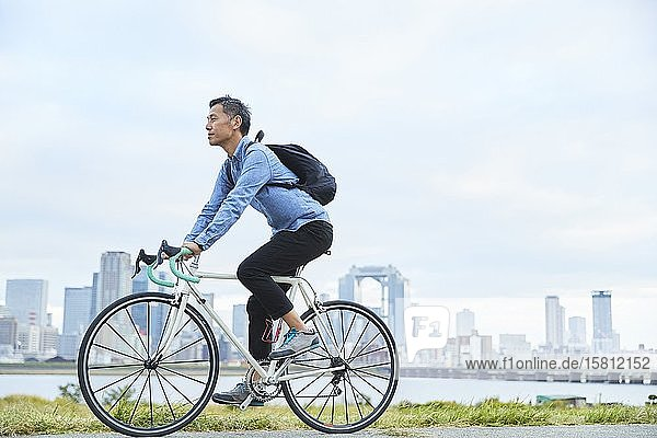 Mature Japanese man with bike downtown Osaka  Japan